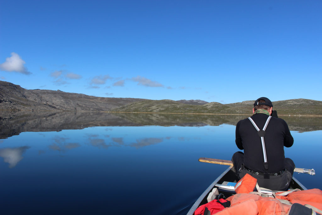 A guy on canoe on the lake on Arctic circle trail with bright sky