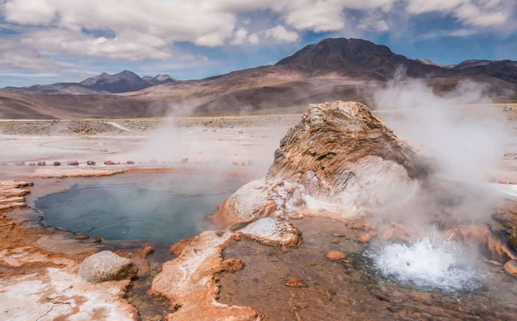 Boiling geothermal pool with a volcano in background in Atacama desert