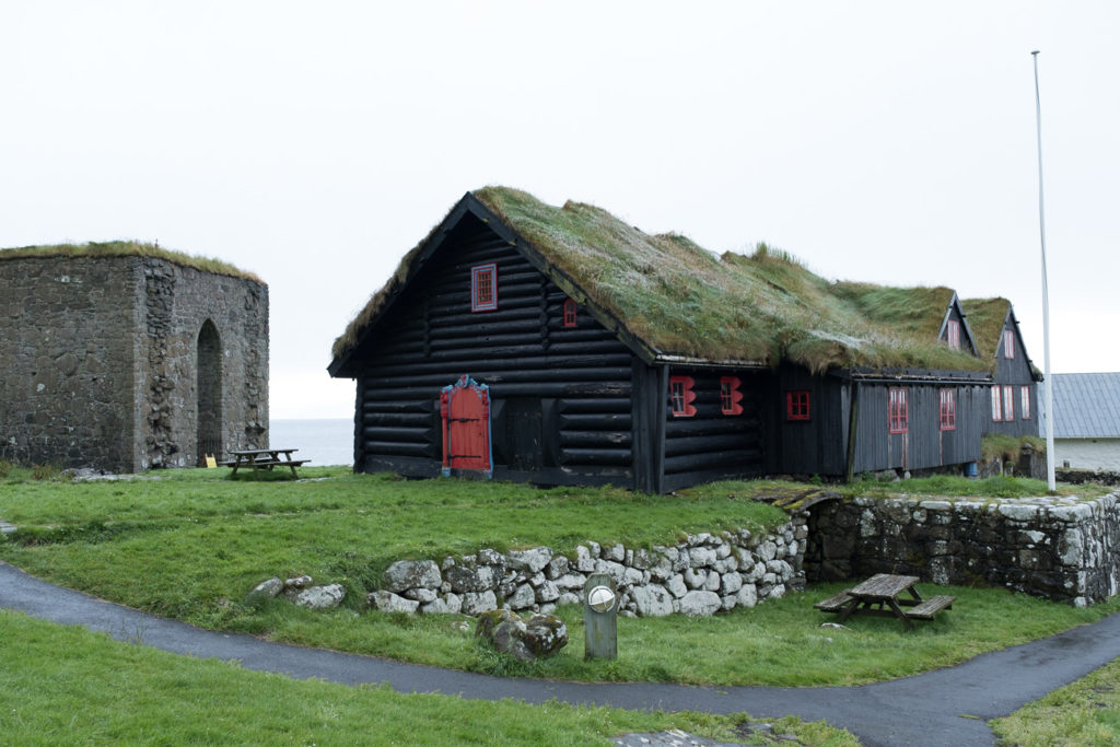 Turfhouse and old stone church in Kirkubour