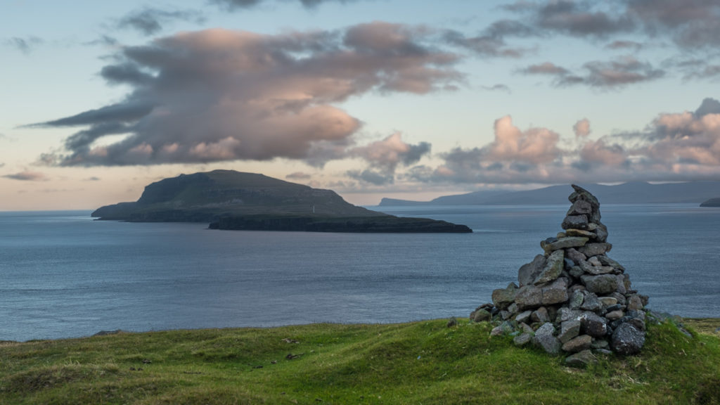 stone cairn infront of the ocean and islands