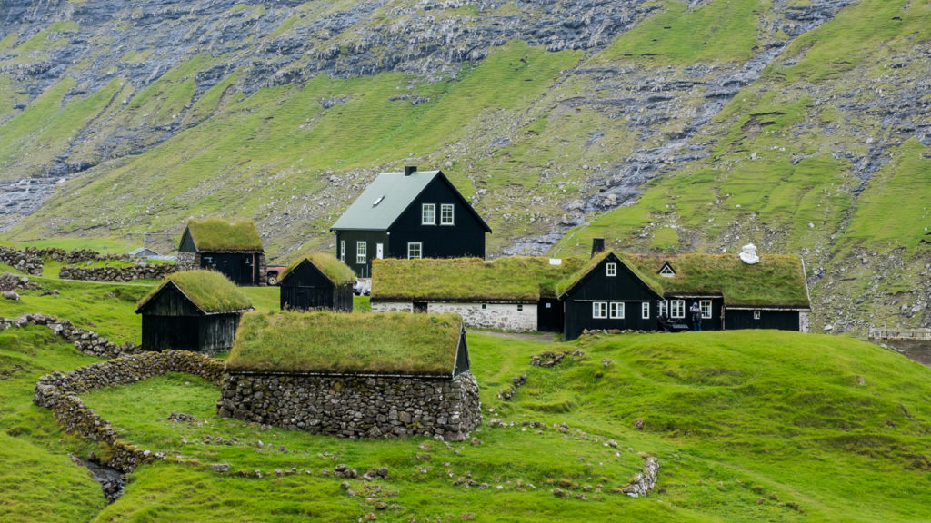 green turf houses with mountain backgroud in Saksun