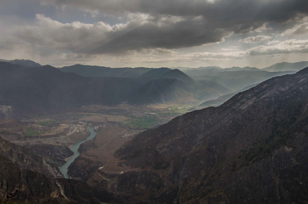Heavy clouds and sun beams shining to the valley in Tiger leaping gorge