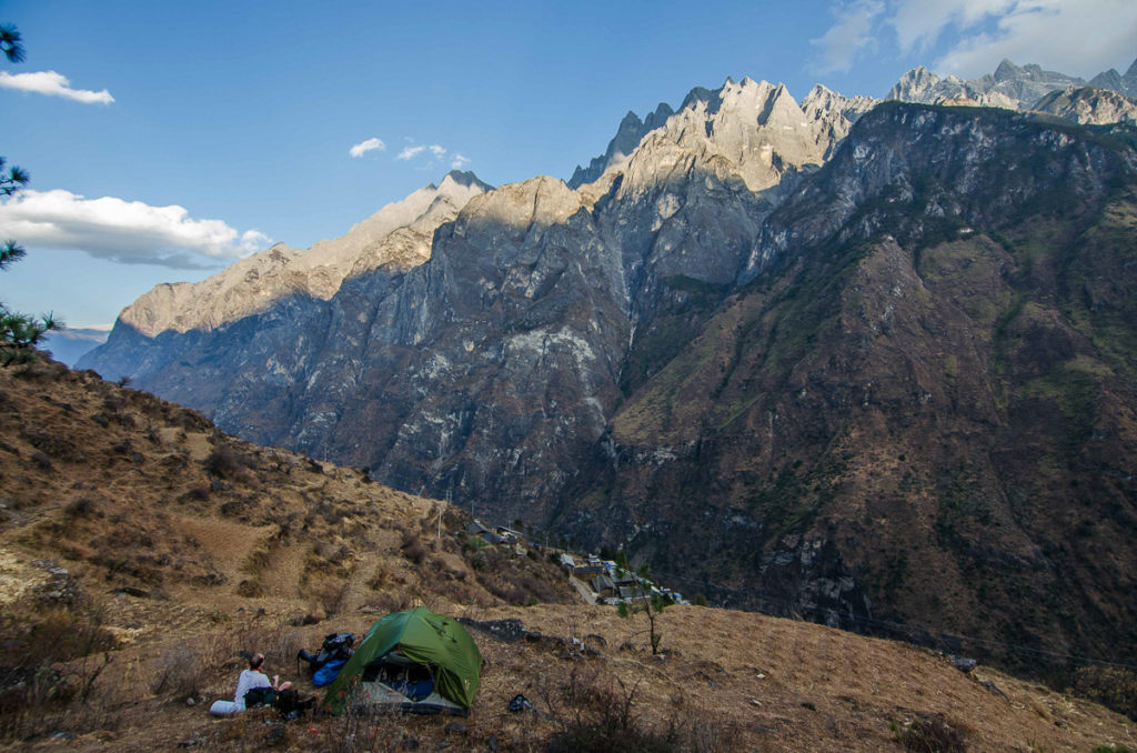 A guy next to the tent observing a high mountain infront of him