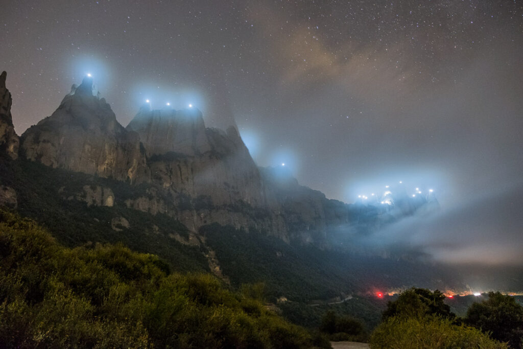 Peaks at night with lights on the top of them with mist