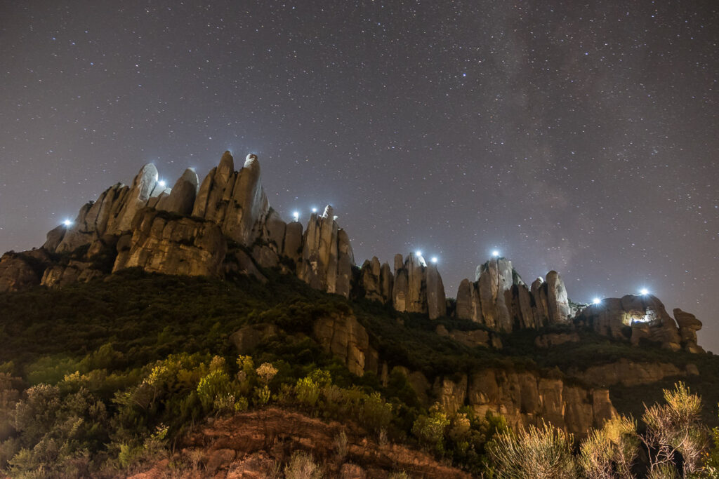 Rugged peaks at night with lights on top of peaks