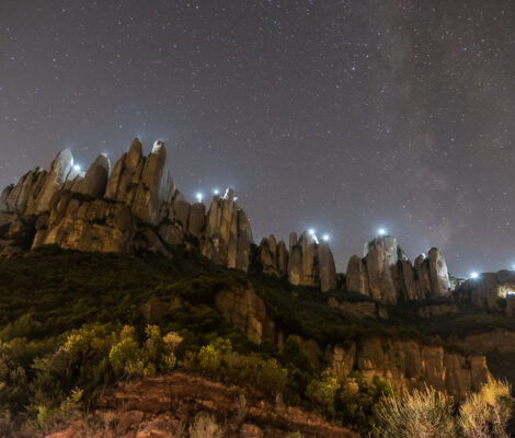 Rugged peaks of Montserrat at night with lights on top of peaks