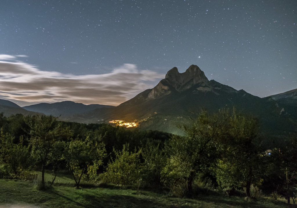 Pedraforca mountain at night with small village under the peak