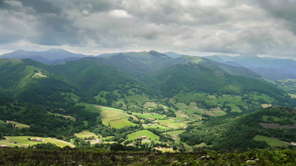 Green valley in Pyrenees in Basque country with farmhouses down