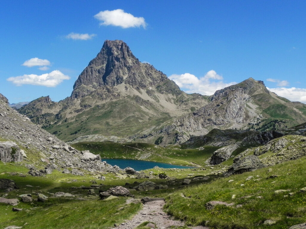 rocky path of Pyrenean Haute Route leading towards the blue lake with sharp rocky mountain in background