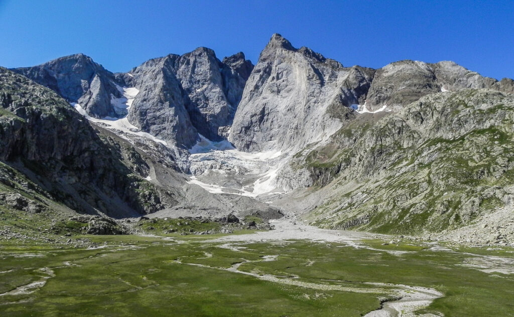 Grassy platteou with a high peak and glaciers in background of Pyrenean Haute Route