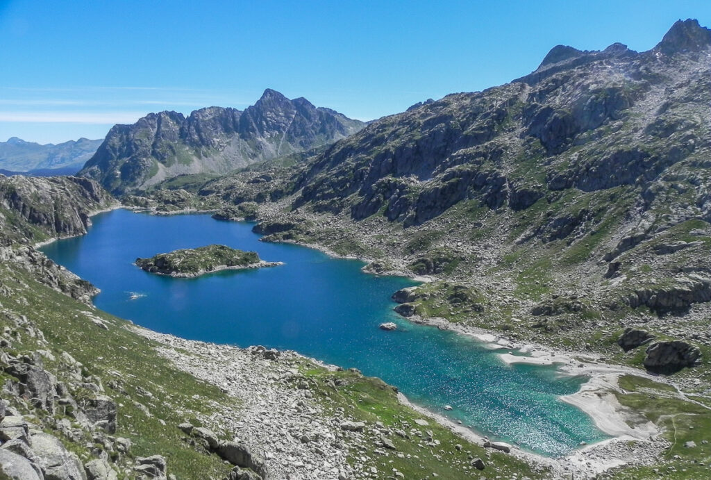 deep blue on Pyrenean Haute Route lakewith a island in the middle surrounded by high mountains