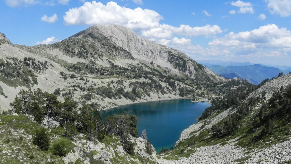 deep blue lake on the foot of the high mountin with blue sky and clouds in background