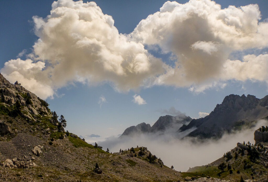 mist in the valley surrounded by mountains and a cloud in the sky on Pyrenean Haute Route