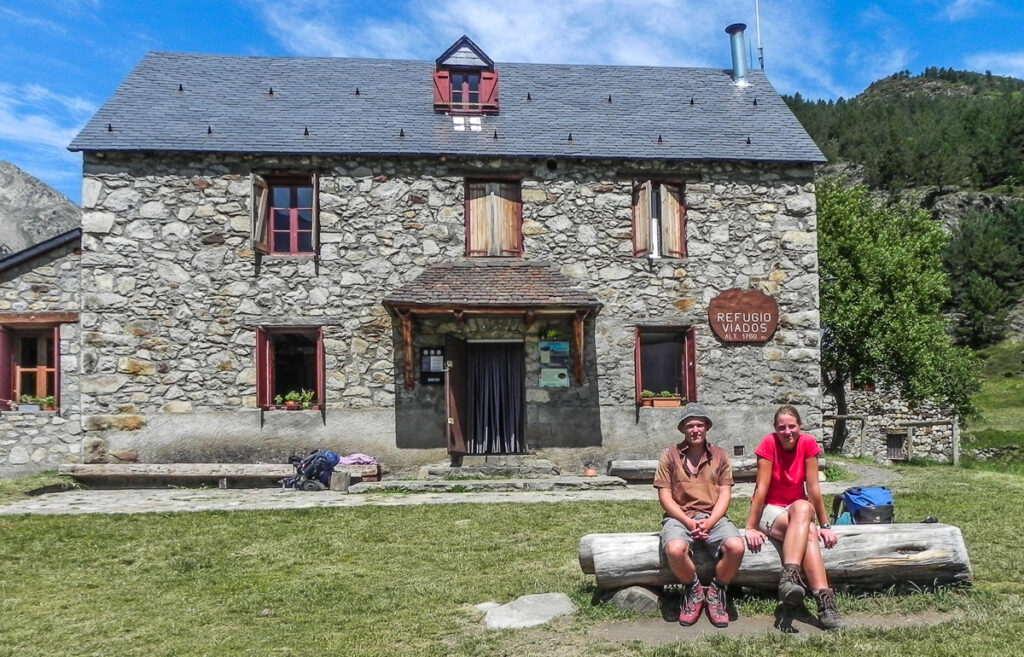 Two persons siting infron of the stone house on Pyrenean haute route