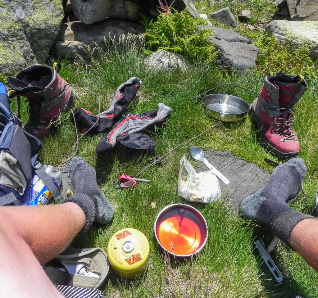Outdoor kitchen with a lot of stuff around on the grass on Pyrenean Haute Route