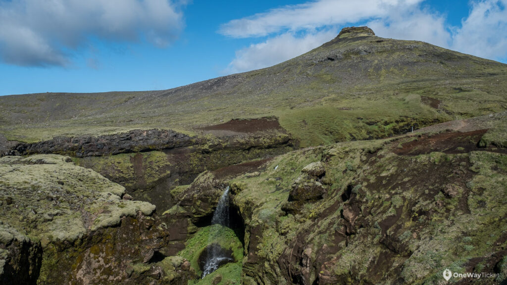Green peak in Iceland on the way up to the volcano with small waterfall in foregroud flowing to Skogafoss