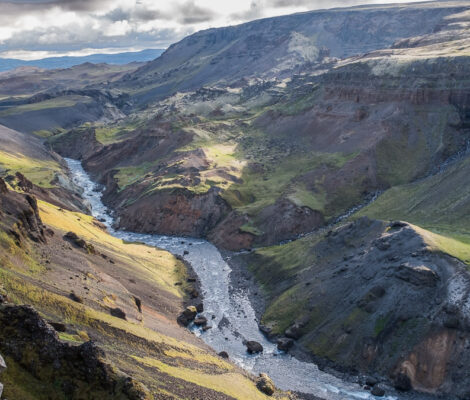 a river in the valley in the Iceland with waterfall on the other side falling down the river