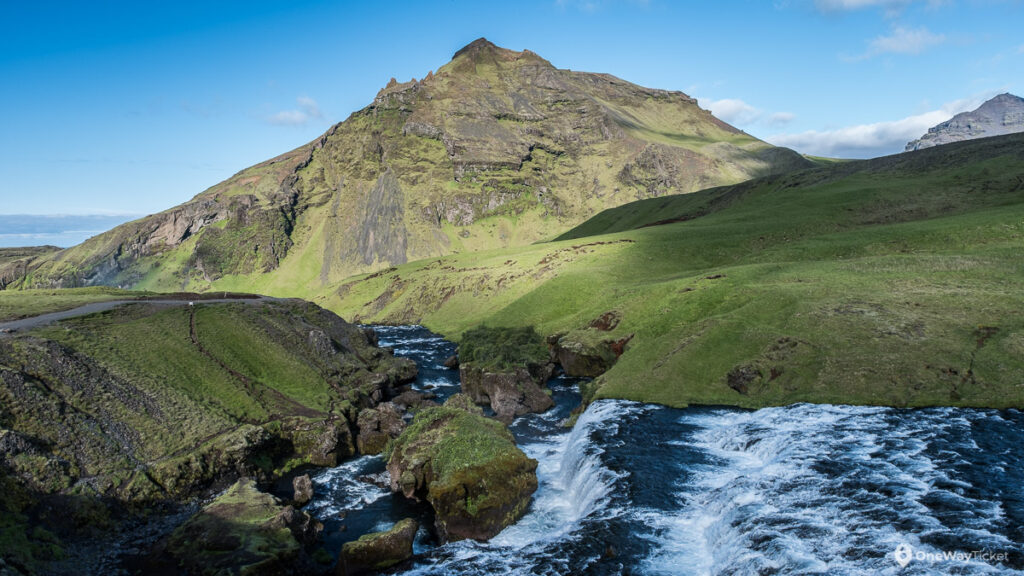 river flowing down towards Skogafoss with green hills around the valley