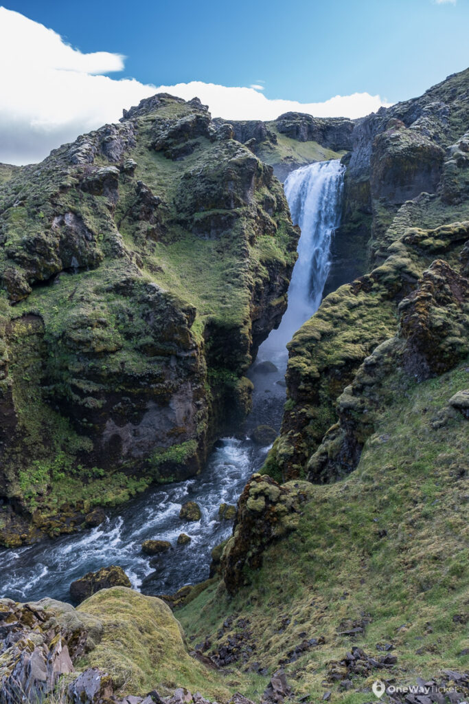 high waterfall dropping from the cliff in Iceland on Fimmvorduhals Hike near Skogafoss