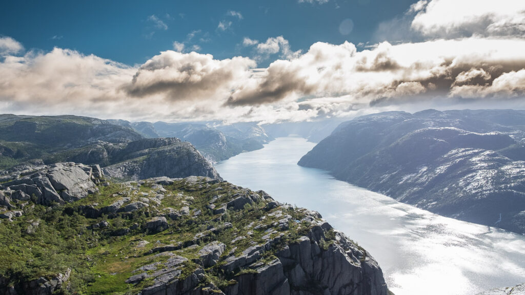 distant view deep to the Lysefjord in norway with heavy yellow clouds above mountains