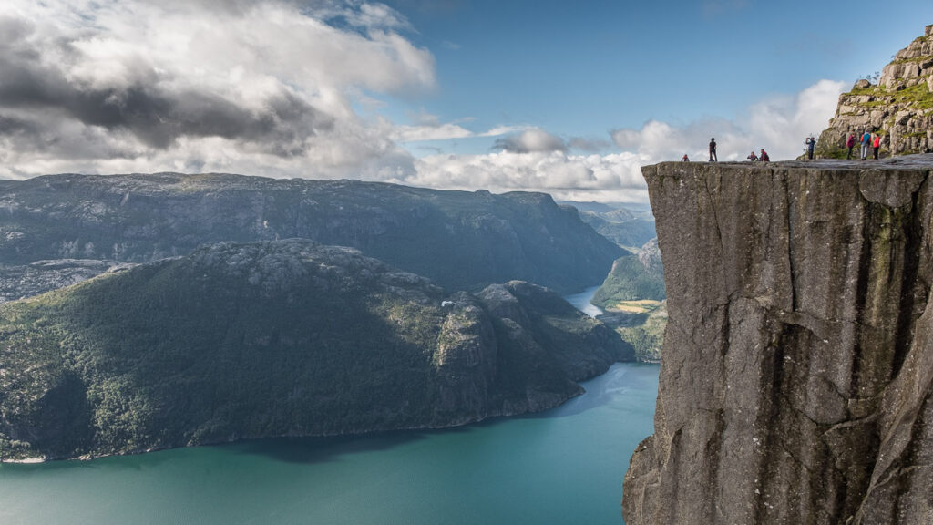 People stanfing at the top of Preikestolen cliff above the blue fjord