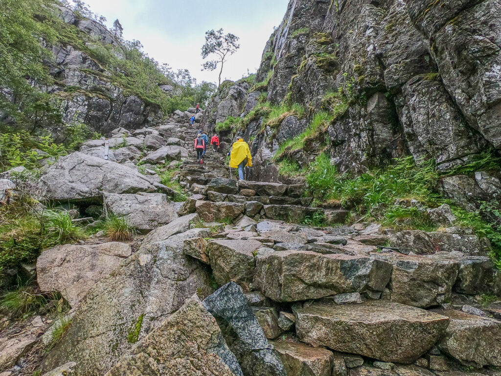 People ascending the steep rocky path in nordic nature to Preikestolen