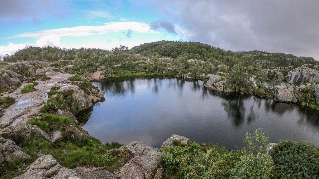 Nice lake surrounded by rocky shore in the middle of nordic nature with few trees around