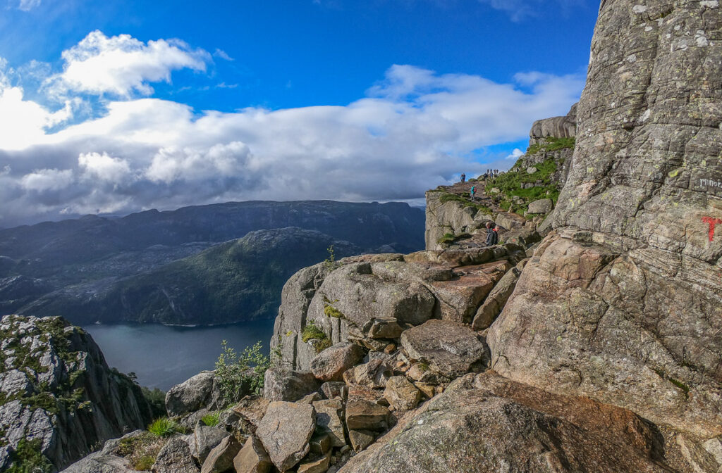 people hiking towards Pulpit rock on a high leveled exposed path on the edge of the cliff above the fjord