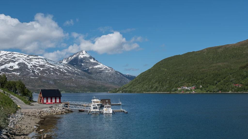 Fjord in northern Europe with red fisherman house in the from and high mountain with snow in the back