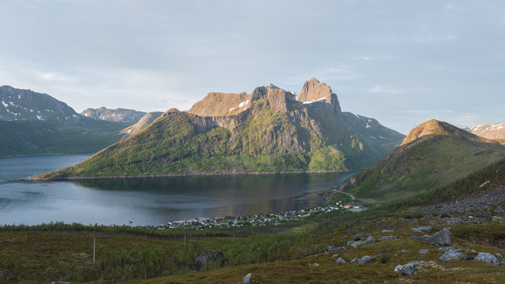 small fisherman village in arctic fjord with a mountain ligheted by the rising sun in behind