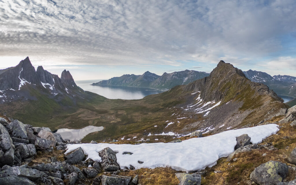 distant views to the fjord on island Segla from the Hesten peak with snow in the forefront and sharp peaks in background