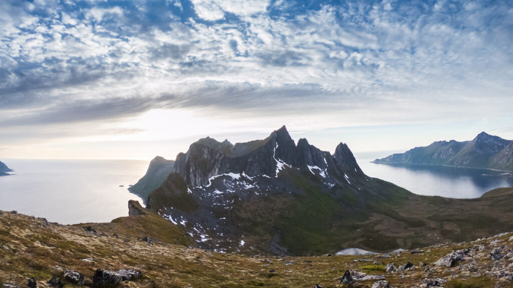 Sunrise over arctic fjord in Norway with spikey group of mountain surrounded by arctic ocean