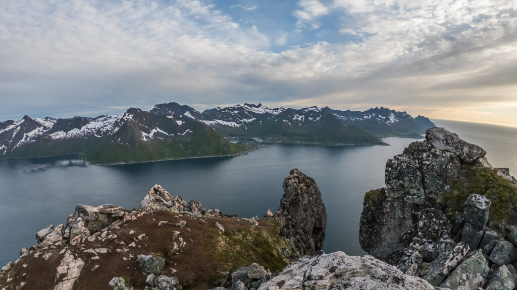 Distant view of island Senja and it´s arctic peaks with some snow on it with an ocean under