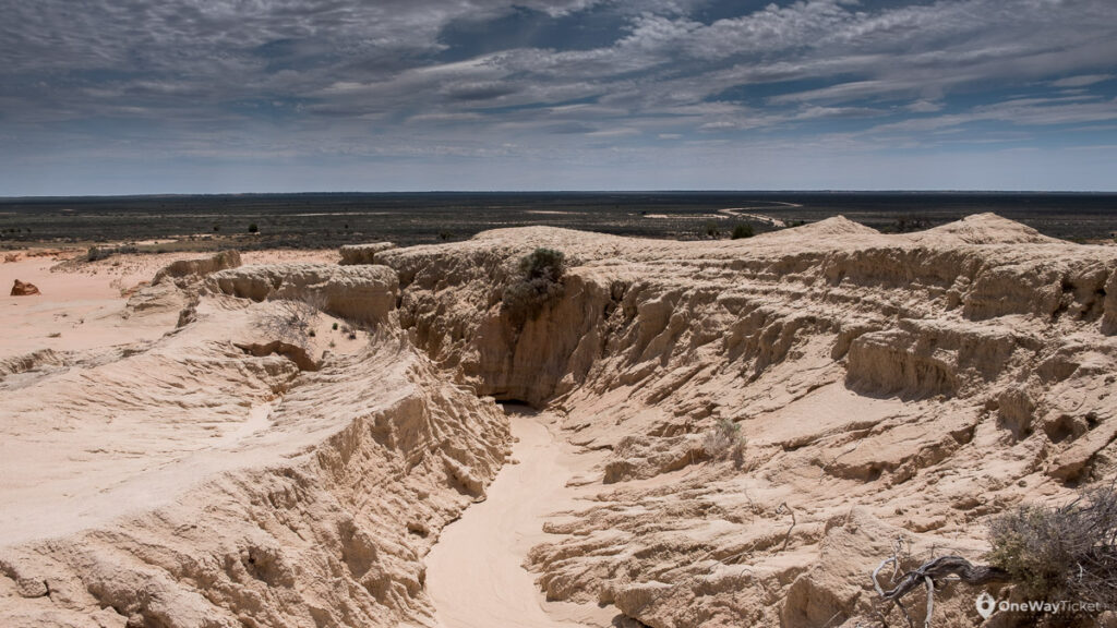 deep ravines in Mungo National Park fromed by water and wind with wast Australian outback in behind with blue sky