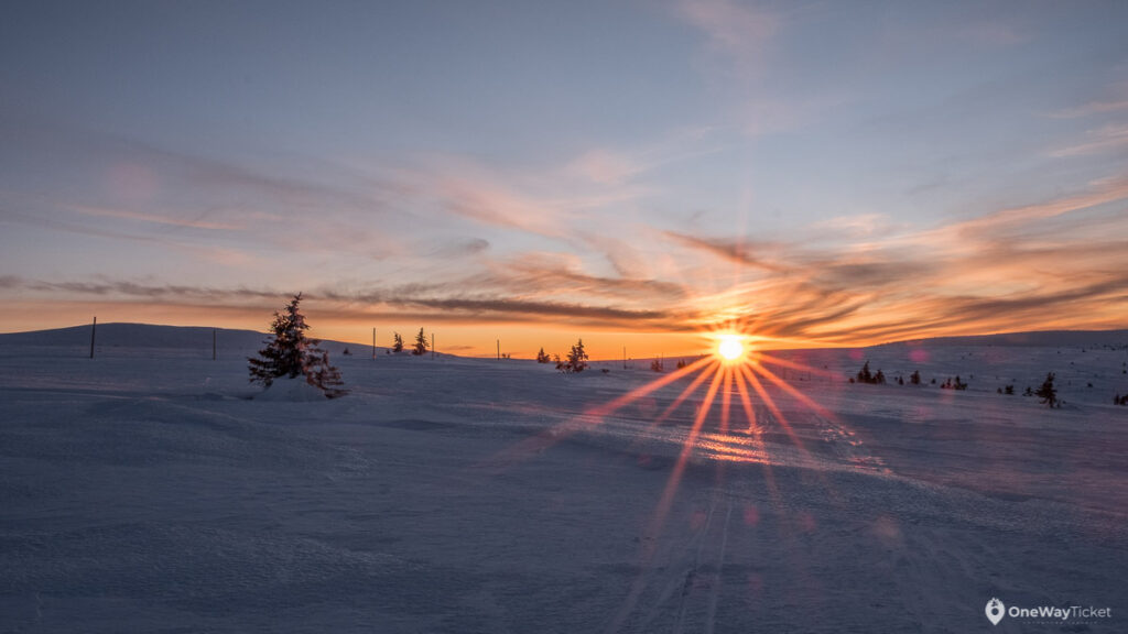 Sun setting over the horizon of altiplano in snowy Czech mountains Krkonose