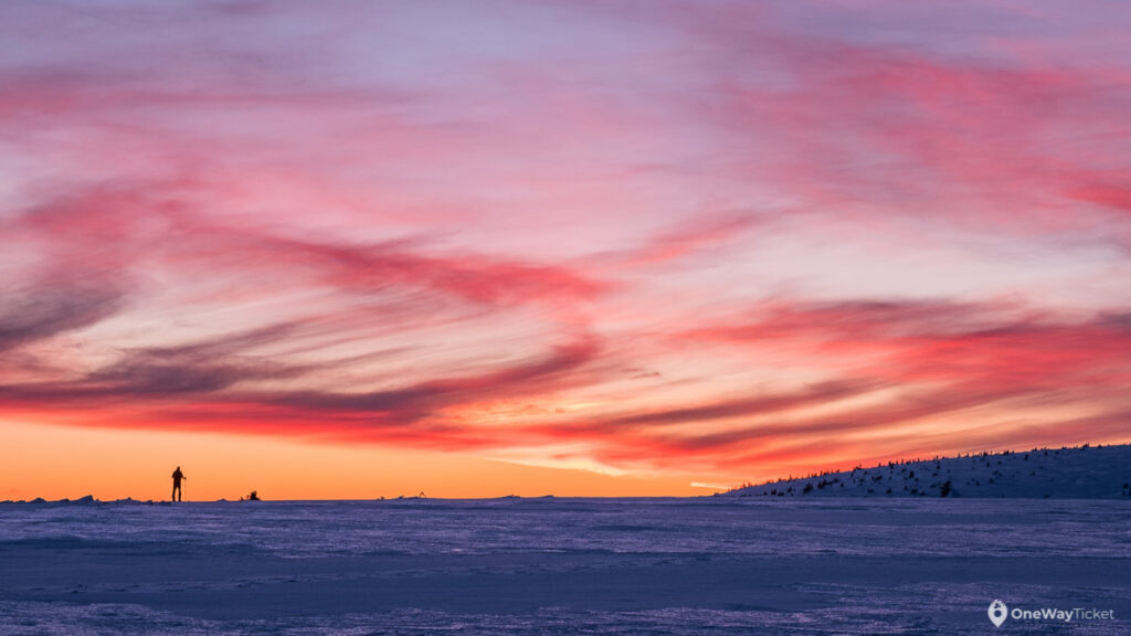 Colorful sunset over Krkonose on expedition with the pulks and silhouete of a skier on the horizon