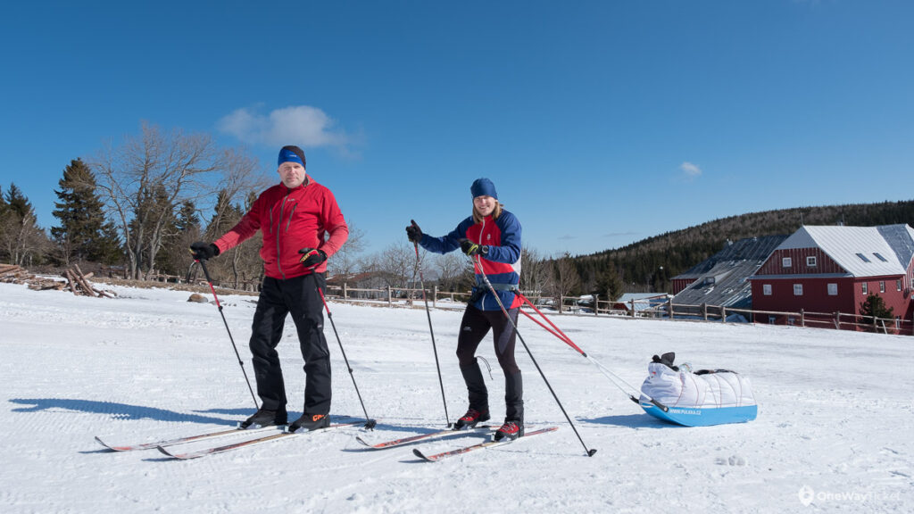 two skiers at starting the expedition with the pulk to do Krkonose winter crossing in Czech mountains