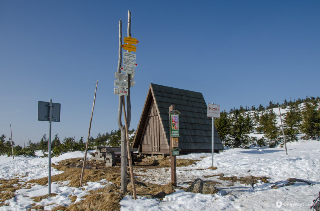 The emergency shelter Pod Smielczem in Krkonose with signpost infront