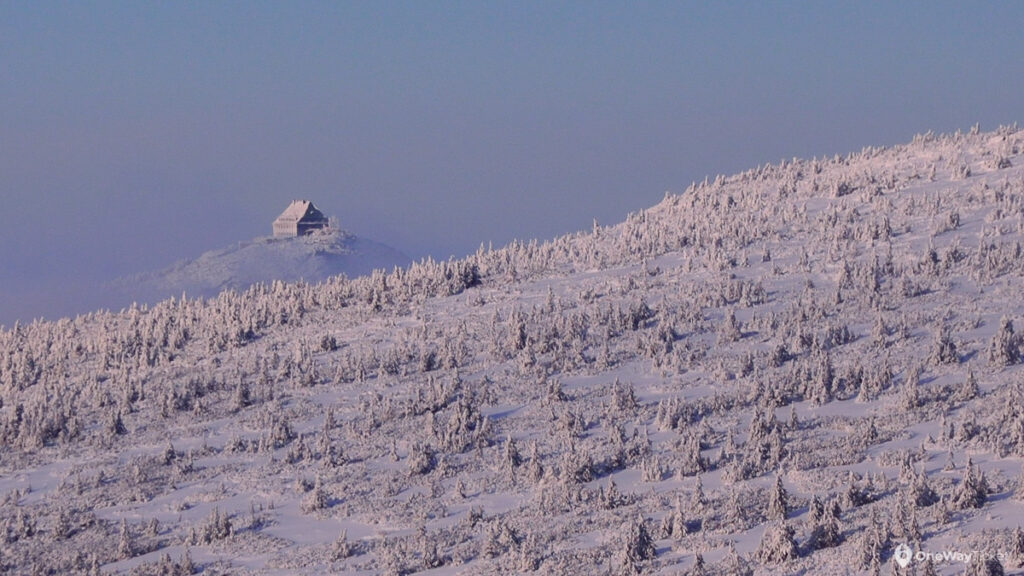 Famous mountain hut in Krkonose mountains in distanfe with steep snowy hill covered by spruce trees