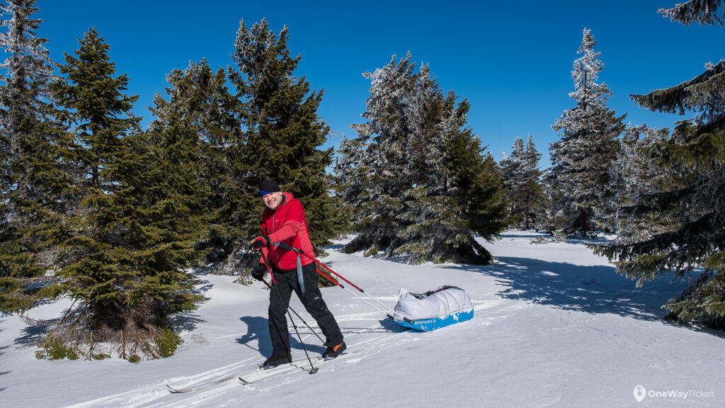 Man pulling the nordic sled in the winter nature of Krkonose on the expedition with the pulk