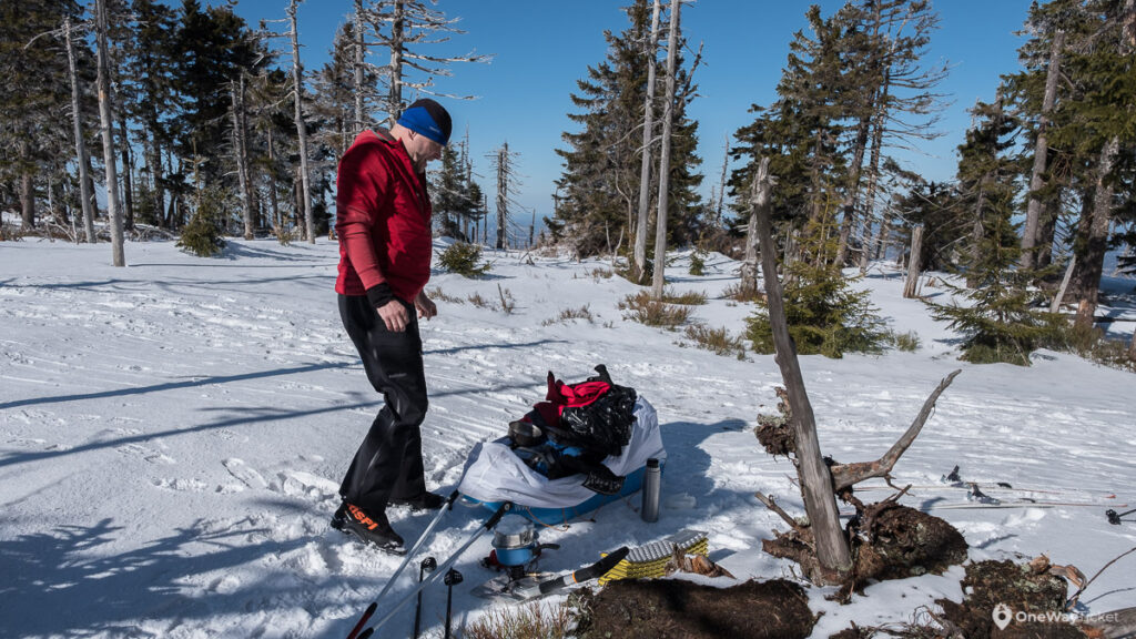 Man melting a water during winter expedition with the pulk in frozen nature in the forest