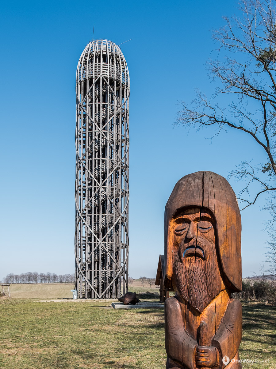 wooden lookout tower with wooden statue in forefront